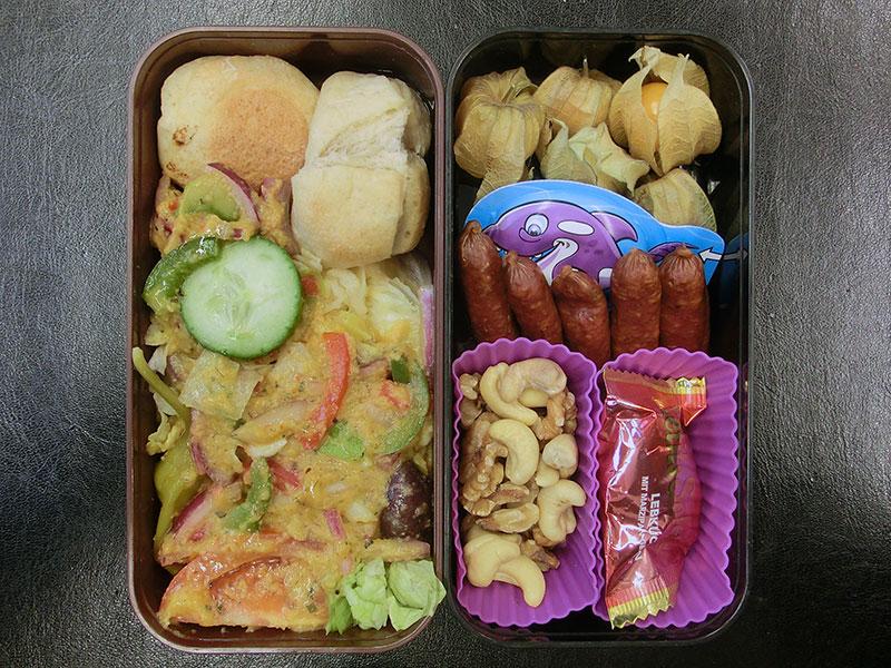 Bento Box gefüllt mit Salat, Brötchen, Physalis, Käse, Salami, Nüsse, Schokolade