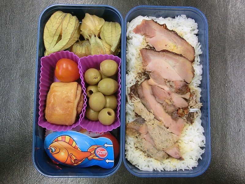 Bento Box gefüllt mit Putenbraten, Reis, Oliven, Gebäck, Schokolade, Physalis