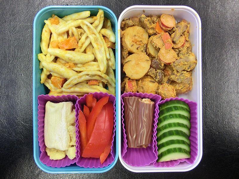 Bento Box gefüllt mit Nudelsalat, Kartofelpfanne, Gurke, Schokolade, Paprika, Ziegenkäse