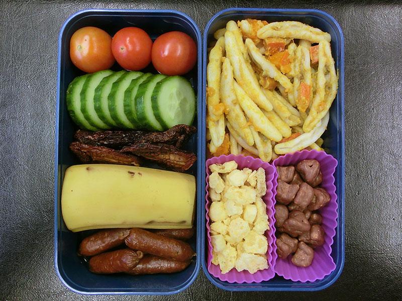 Bento Box gefüllt mit Nudelsalat, Käse, Schokolade, Tomaten, Gurke, Getrocknete Tomaten, Banane, Salami