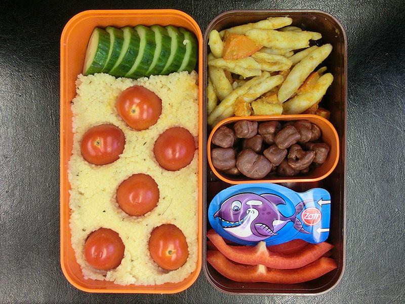 Bento Box gefüllt mit Cous Cous, Tomaten, Gurke, Paprika, Käse, Schokolade, Nudelsalat