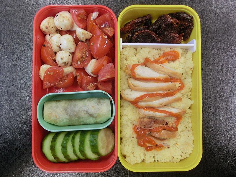Bento Box gefüllt mit Tomaten, Mozzarella, Wrap, Gurke, Getrocknete Tomaten, Cous Cous mit Hühnchen