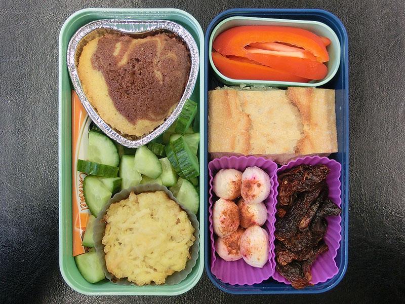 Bento Box gefüllt mit Gurke, Kuchen, Auflauf, Schokolade, Brot, Paprika, Mozzarella, Getrocknete Tomaten