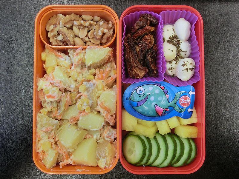 Bento Box gefüllt mit Kartoffelsalat, Nüsse, Getrocknete Tomaten, Mozzarella, Käse, Ananas, Gurke