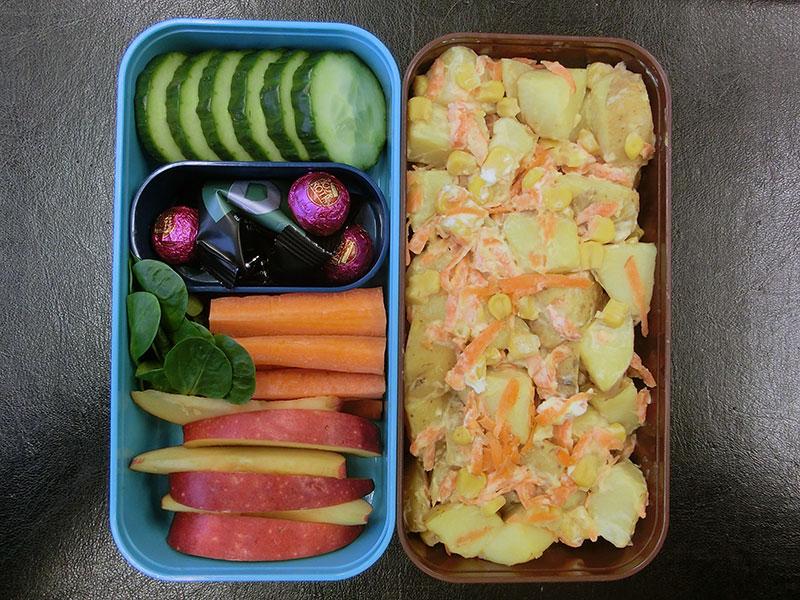 Bento Box gefüllt mit Kartoffelsalat, Gurke, Schokolade, Möhren, Apfel