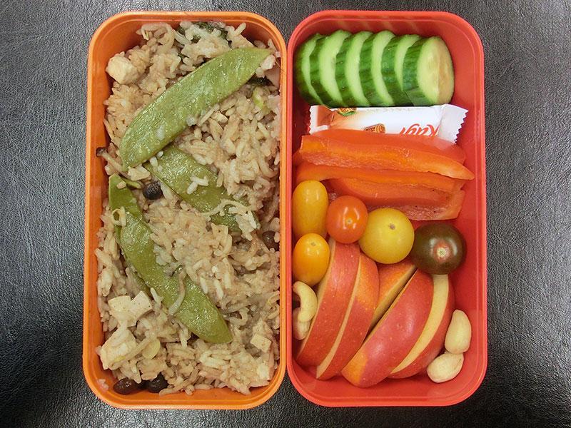 Bento Box gefüllt mit Paprika, Tomaten, Gurke, Schokolade, Apfel, Nüsse, Asiapfanne