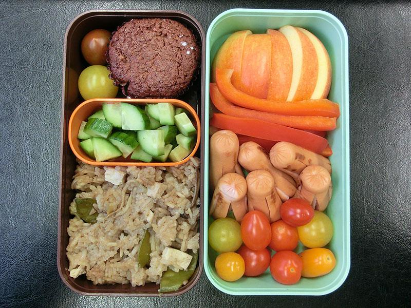Bento Box gefüllt mit Würstchen, Tomaten, Paprika, Apfel, Gurke, Asia-Pfanne, Muffin