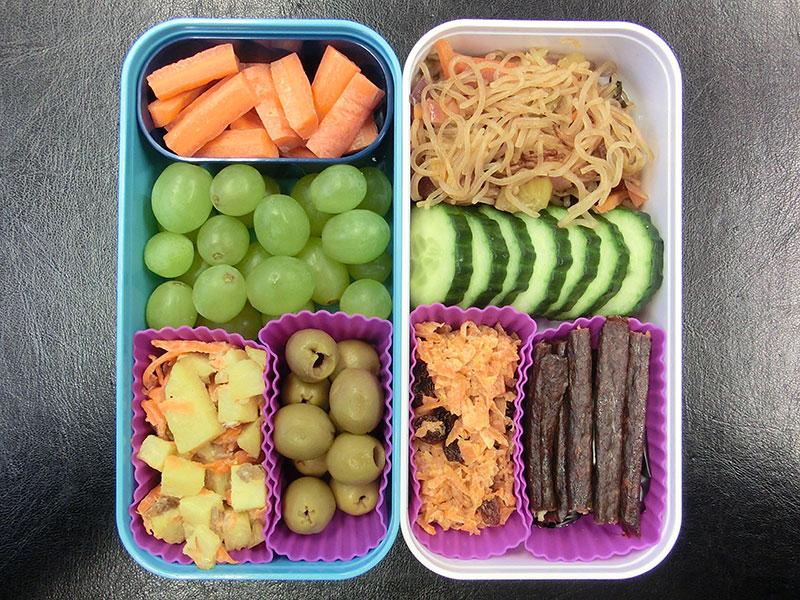 Bento Box gefüllt mit Oliven, Kartoffelsalat, Weintrauben, Karotten, Glasnudelsalat, Gurke, Indisches Karotten-Halva, Galloway Sticks, Schokolade