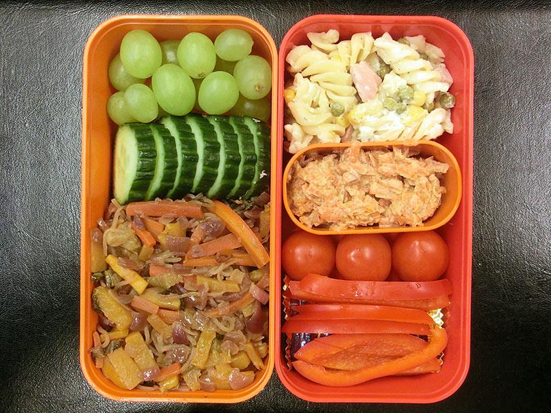 Bento Box gefüllt mit Weintrauben, Gurke, Glasnudelsalat, Nudelauflauf, Indisches Karotten-Halva, Tomaten, Paprika, Schokolade
