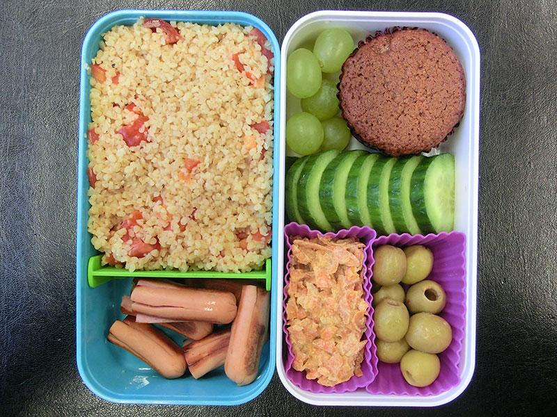 Bento Box gefüllt mit Bulgur, Würstchen, Indisches Karotten-Halva, Oliven, Gurke, Weintrauben, Muffin