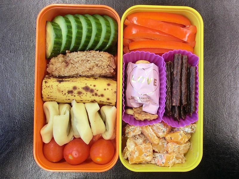 Bento Box gefüllt mit Tomaten, Gurke, Kuchen, Banane, Tortellini, Paprika, Galloway Sticks, Kürbis, Nüsse, Lakritz