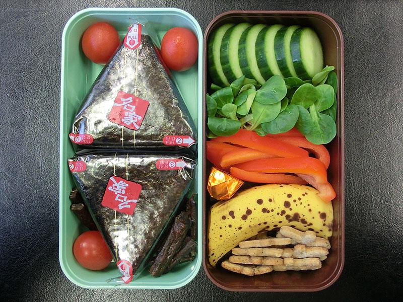 Bento Box gefüllt mit Onigiri, Galloway Sticks, Tomaten, Gurke, Paprika, Schokolade, Banane, Kekse