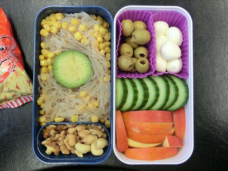 Bento Box gefüllt mit Konjak Nudeln mit Mais, Nüsse, Mozzarella, Oliven, Gurke, Apfel