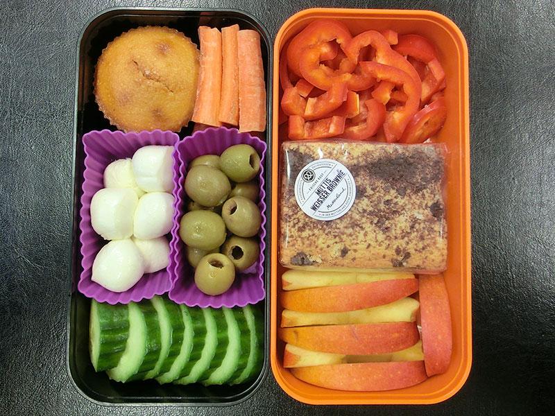 Bento Box gefüllt mit Gurke, Mozzarella, Oliven, Muffin, Karotte, Paprika, Muttis Weißer Brownie, Apfel