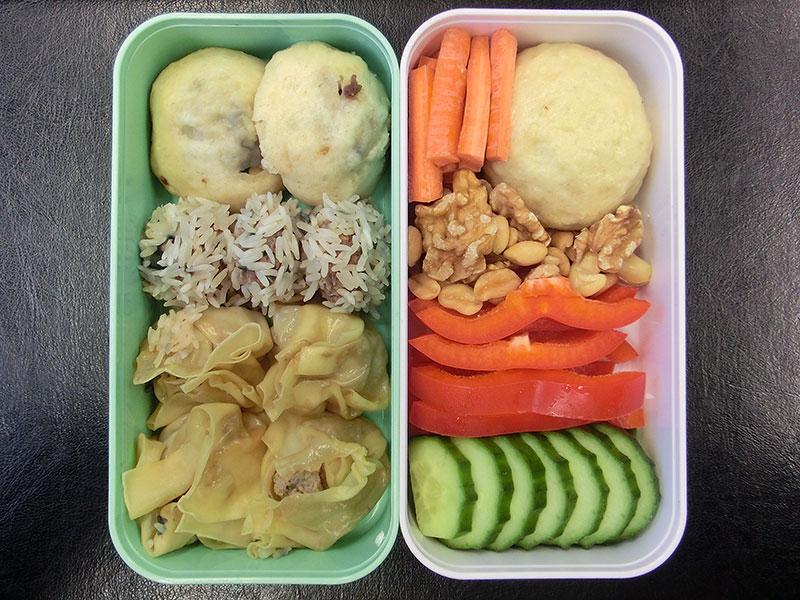 Bento Box gefüllt mit Dim Sum, Nüsse, Paprika, Karotten, Gurke