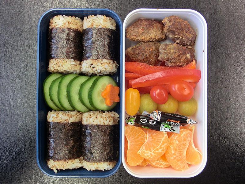 Bento Box gefüllt mit Onigiri, Gurke, Hackbällchen, Paprika, Tomaten, Mandarine