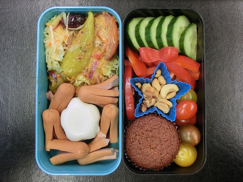 Bento Box gefüllt mit Ei, Würstchen, Salat, Muffin, Tomaten, Paprika, Nüsse, Gurke