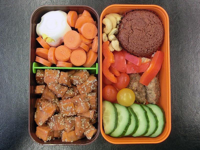 Bento Box gefüllt mit Gurke, Hackbällchen, Tomaten, Paprika, Muffin, Nüsse, Karotten, Ei, Süßkartoffeln