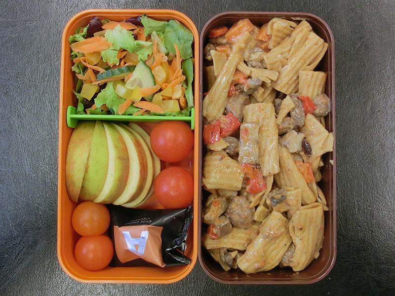 Bento Box gefüllt mit Putenpfanne, Tomaten, Apfel, Salat, Lakritz