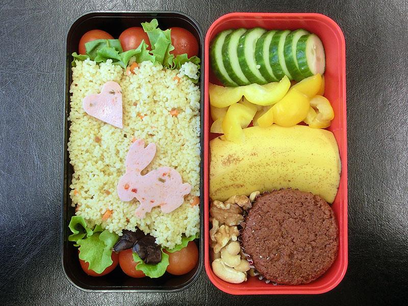 Bento Box gefüllt mit Paprika, Gurke, Banane, Nüsse, Muffin, Cous Cous, Tomaten