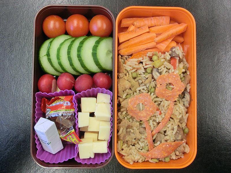 Bento Box gefüllt mit Tomaten, Gurke, Radieschen, Käse, Weingummi, Schokolade, Karotten, Reispfanne