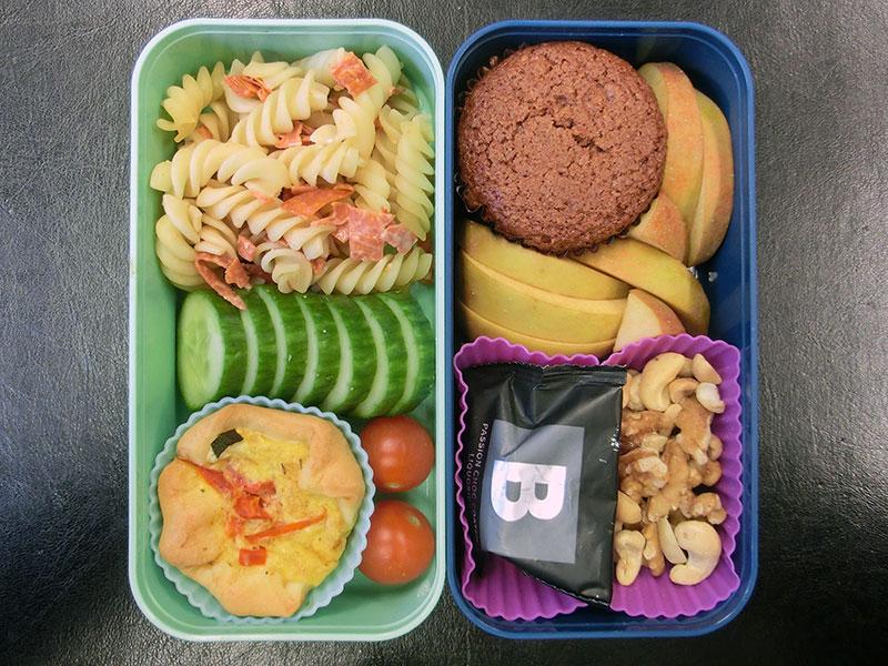 Bento Box gefüllt mit Nudelauflauf, Tomaten, Quiche, Muffin, Apfel, Nüsse, Lakritz, Schokolade