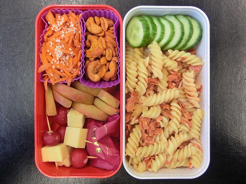 Bento Box gefüllt mit Nudelsalat, Gurke, Nüsse, Karotten, Apfel, Käse, Radieschen, Lakritze