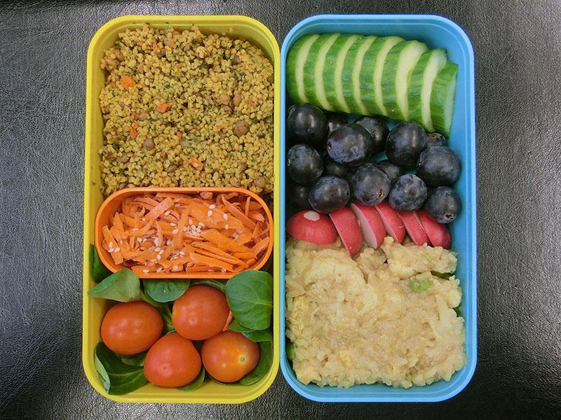 Bento Box gefüllt mit Blumenkohlpfanne, Radieschen, Weintrauben, Gurke, Cous cous, Möhren, Tomate