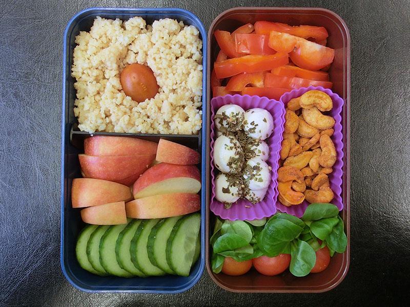 Bento Box gefüllt mit Tomaten, Mozzarella, Nüsse, Cous Cous, Äpfel, Gurke, Paprika
