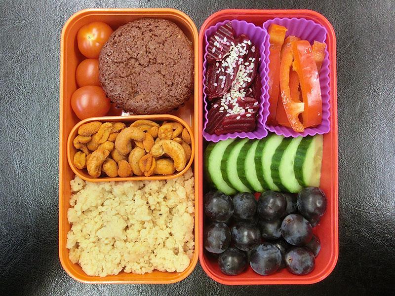 Bento Box gefüllt mit Rote Beete, Paprika, Gurke, Weintrauben, Muffin, Tomaten, Nüsse, Cous Cous