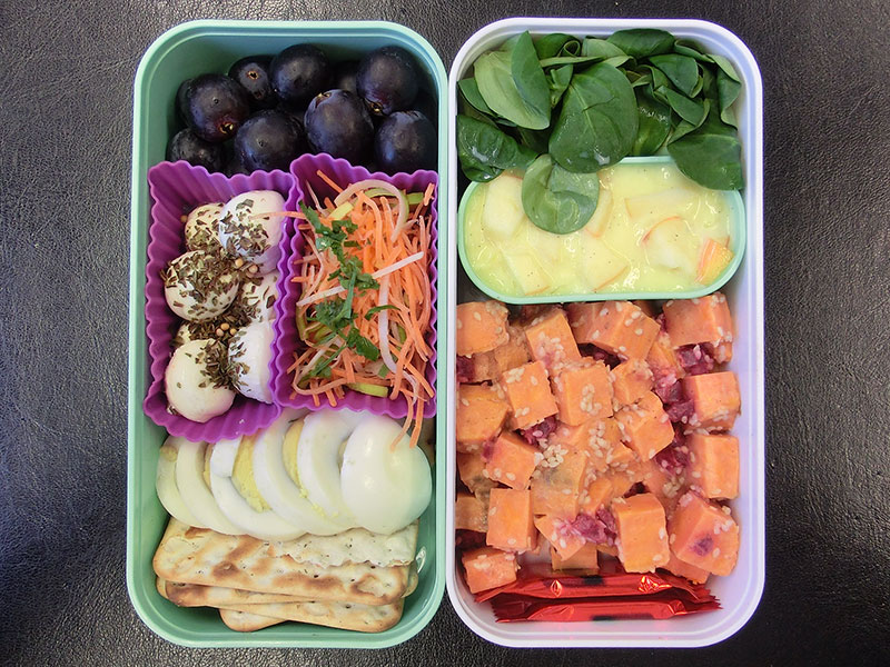 Bento Box gefüllt mit Apfel , Custard, Süsskartoffeln, Weintrauben, Mozzarella, Karotten, Ei, Cracker