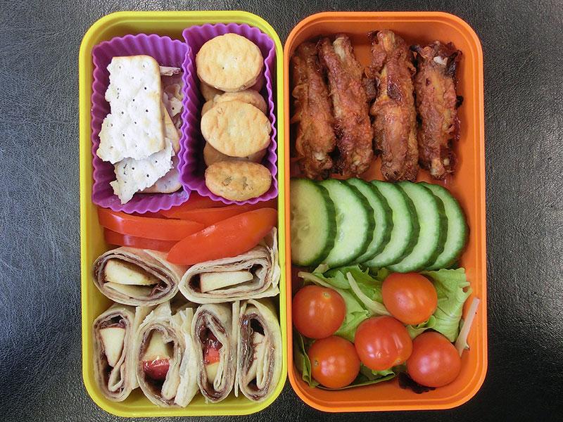 Bento Box gefüllt mit Tomaten, Gurke, Chicken Wings, Cracker, Paprika, Wraps