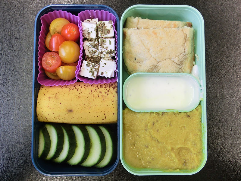 Bento Box gefüllt mit Muss, Dipp, Brot, Schafskäse, Tomaten, Banane, Gurke