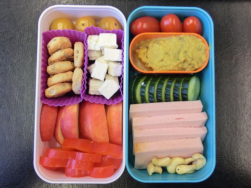 Bento Box gefüllt mit Paprika, Apfel, Schafskäse, Cracker, Tomaten, Muss, Gurke, Leberkäse, Nüsse