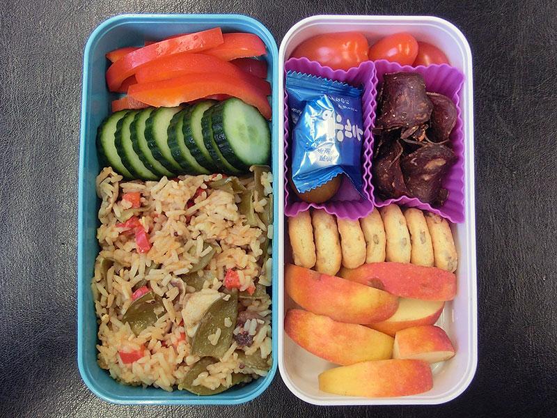 Bento Box gefüllt mit Paprika, Gurke, Reispfanne, Tomaten, Galloway-Chips, Cracker, Apfel