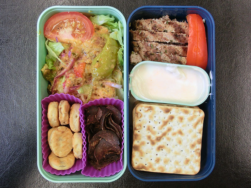 Bento Box gefüllt mit Galloway Chips, Cracker, Salat, Hacksteak, Dipp, Paprika