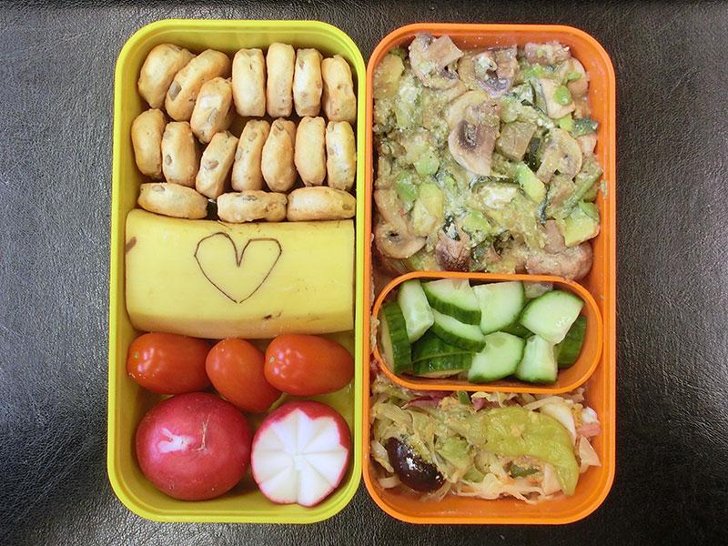 Bento Box gefüllt mit Cracker, Banane, Tomaten, Radieschen, Pilzpfanne, Gurke, Salat