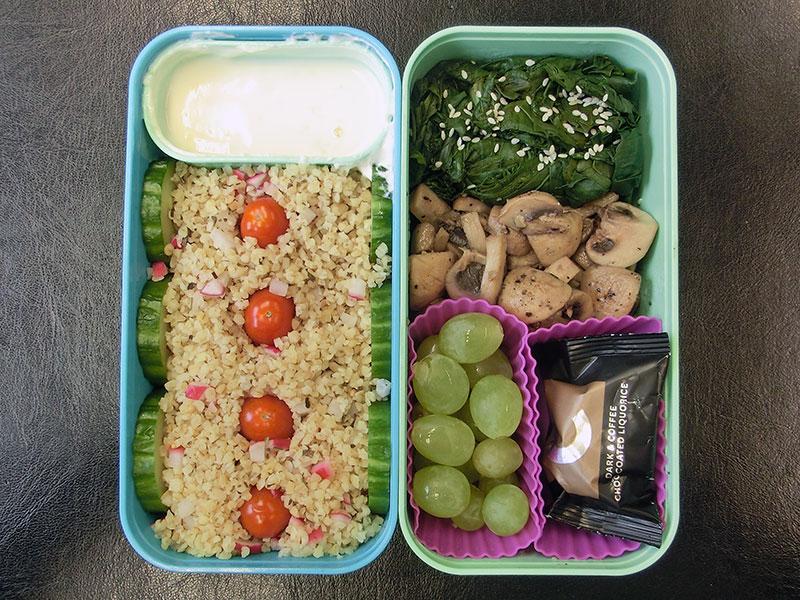 Bento Box gefüllt mit Pilze, Spinat, Weintrauben, Lakritz, Bulgur, Gurke, Dipp, Tomaten