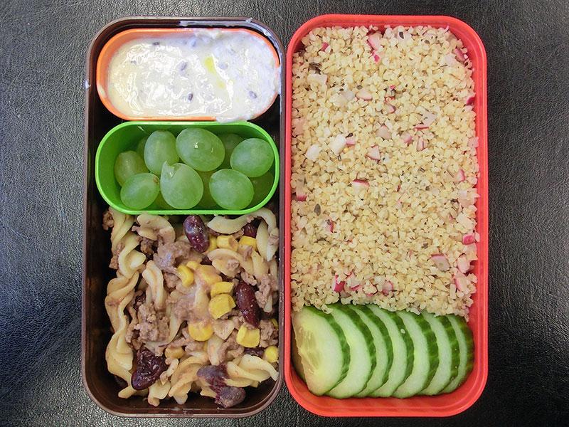 Bento Box gefüllt mit Gurke, Bulgur, Quark, Weintrauben, Chilli con Carne