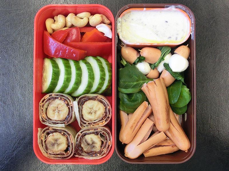 Bento Box gefüllt mit Würstchen, Spinat, Mozzarella, Quark, Nüsse, Paprika, Gurke, Wraps