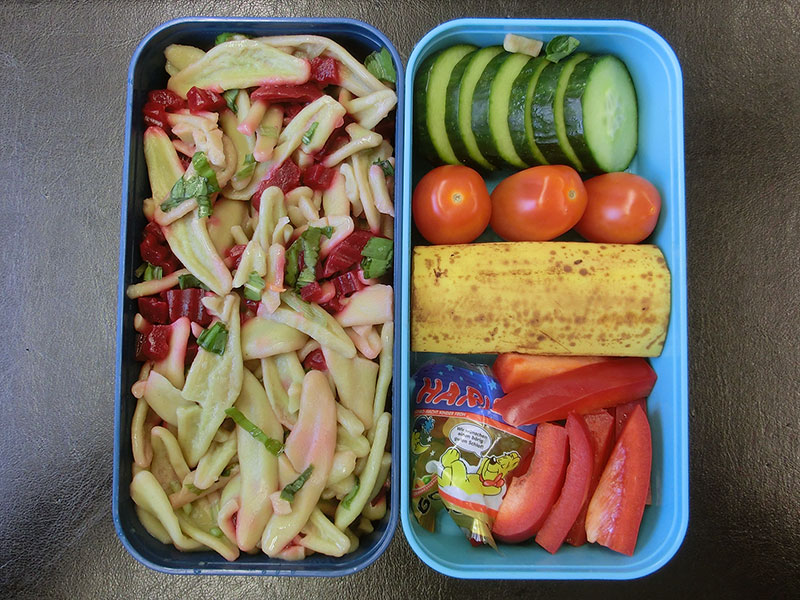 Bento Box gefüllt mit Nudelsalat, Paprika, Gummibärchen, Banane, Tomaten, Gurke