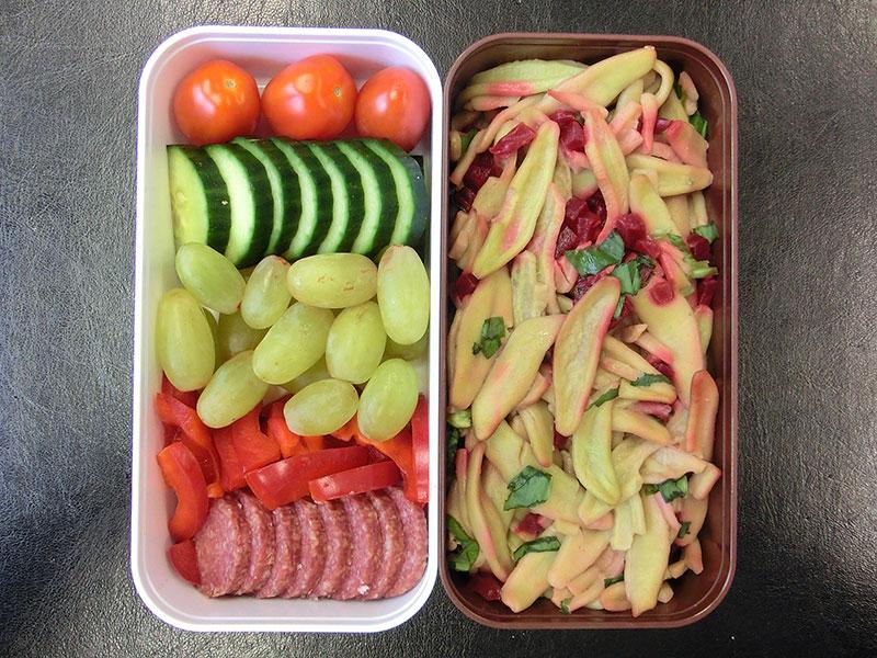 Bento Box gefüllt mit Tomate, Gurke, Weintrauben, Paprika, Salami, Nudelsalat