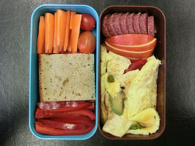 Bento Box gefüllt mit Möhren, Tomaten, Brot, Paprika, Salami, Apfel, Gerührtes Spiegelei