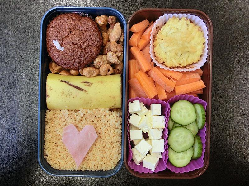 Bento Box gefüllt mit Muffin, Erdnüsse, Banane, Cous Cous, Pie, Möhren, Schafskäse, Gurke