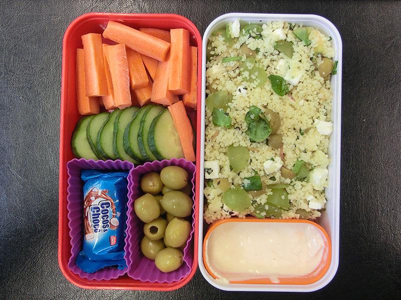 Bento Box gefüllt mit Cous Cous, Dipp, Möhren, Gurke, Oliven, Schokolade