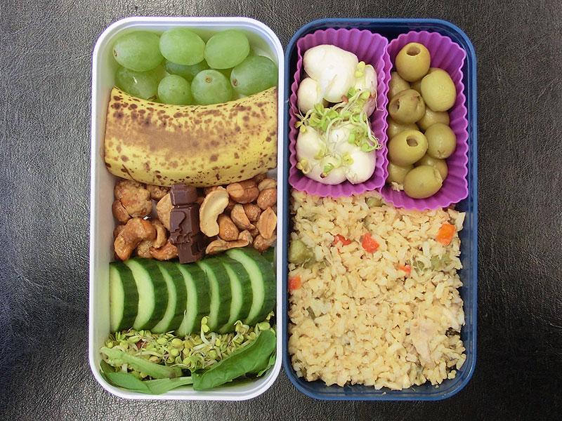 Bento Box gefüllt mit Morzarella Herzen, Oliven, Reispfanne, Weintrauben, Banane, Erdnüsse, Gurke, Sprossen
