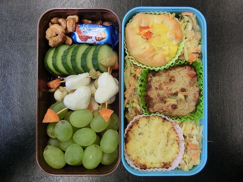 Bento Box gefüllt mit Auflauf, Quiche, Salat, Erdnüsse, Schokolade, Gurke, Mozzarella, Weintrauben