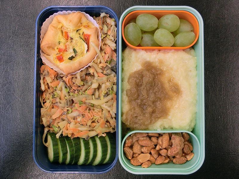 Bento Box gefüllt mit Weintrauben, Milchreis, Erdnüsse, Salat, Gurke, Quiche