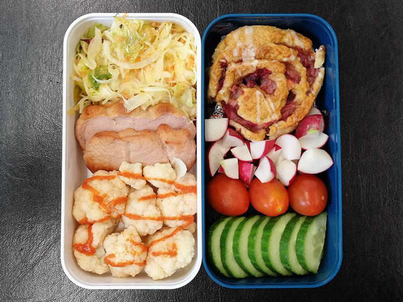 Bento Box gefüllt mit Blumenkohl, Leberkäse, Salat, Erdbeerschnecke, Radieschen, Tomaten, Gurke