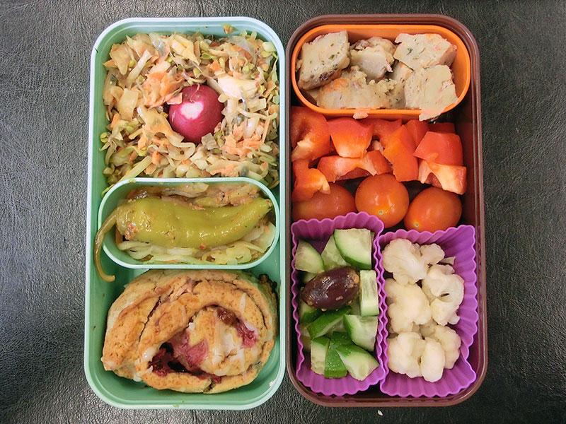 Bento Box gefüllt mit Knödel, Paprika, Tomate, Blumenkohl, Salat, Erdbeerschnecke